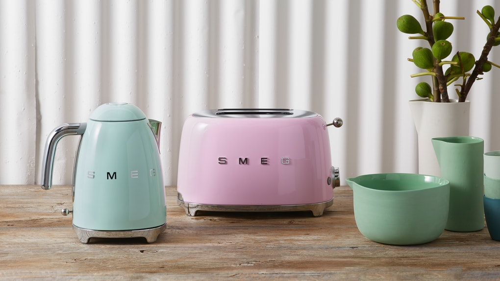 A bunch of colorful SMEG appliances sit on a wooden counter.