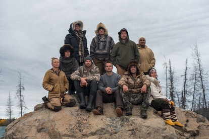 10 outdoorsy competitors sit on a rock in the Arctic.