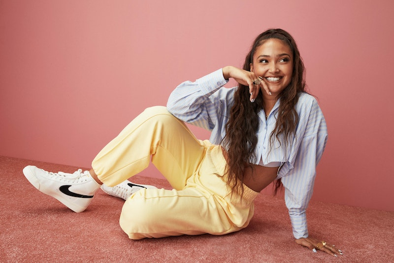Joy Crookes pictured wearing a blue shirt, yellow trousers, and black and white Nike blazers against a  pink backdrop