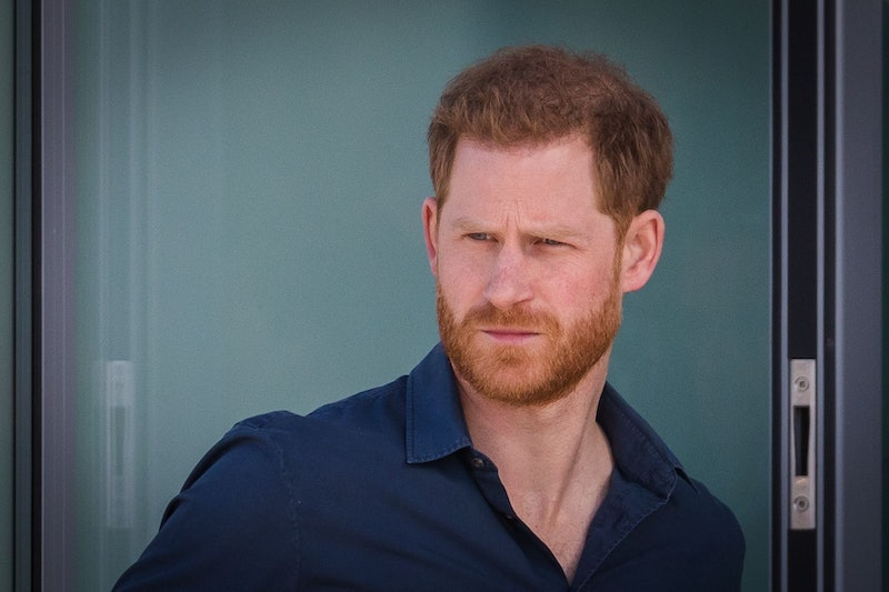 Prince Harry looking concerned wearing a blue shirt