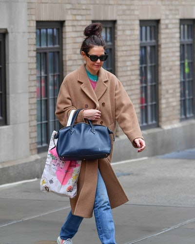 Katie Holmes in a beife coat and handbag while walking in New York City.