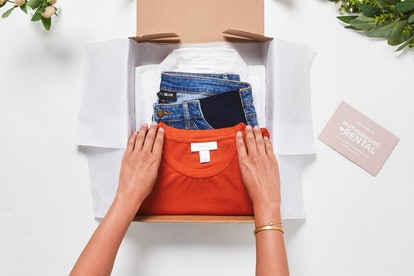 Hands unboxing rented maternity clothes from motherhood rental