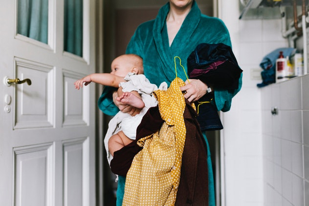 Woman holding clothes, baby, feeling touched out