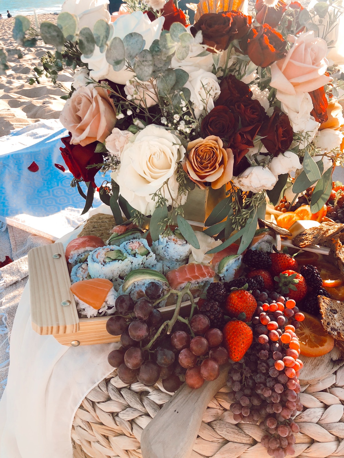 """The Picnic Collective's """"Simple Pleasures"""" package includes a spread of sushi, grapes, flowers, and Bohemian details."""