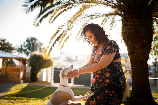 pregnant woman playing in yard with her dog