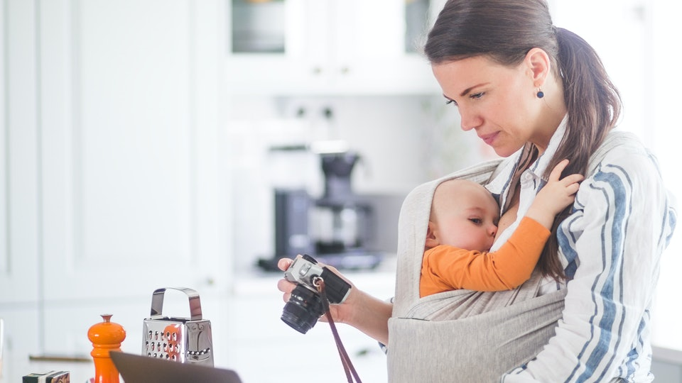 mom breastfeeding baby in a baby carrier while working on her laptop