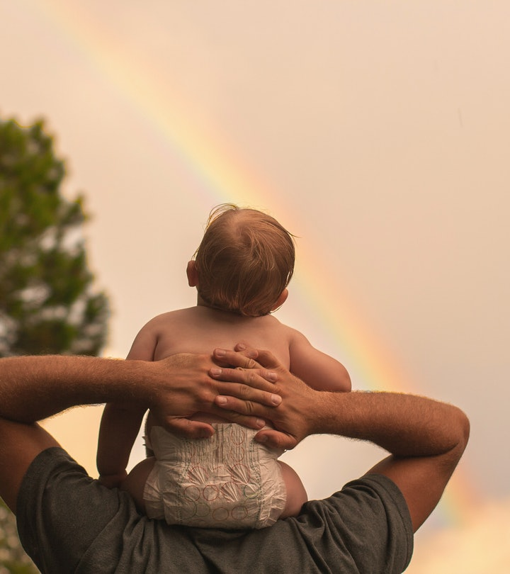 baby sitting on parent's shoulders watching rainbow