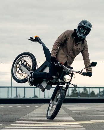 A rider braking and popping up the tail of a Cake Ink SL electric motorcycle