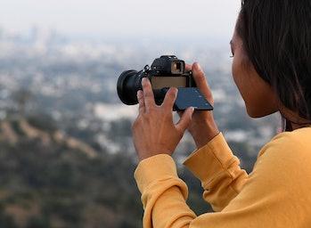 A Black woman using a Nikon Z 50 camera