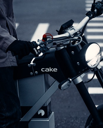 A close-up of the handlebars and front fork of a Cake Ink SL electric motorcycle