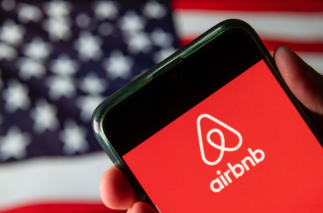 In this photo illustration the American online marketplace and hospitality service Airbnb logo is seen on an Android mobile device with United States of America flag in the background.
