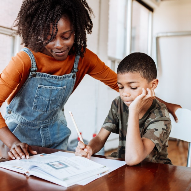 Black mother helping son with homeschooling work
