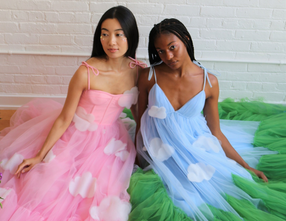 Two women sit on the floor, while wearing dresses from the Disney Princess x Lirika Matoshi collection.