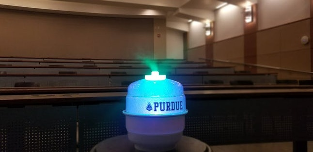 The prototype of device that uses food coloring to neutralize airborne viruses being demonstrated in a classroom.