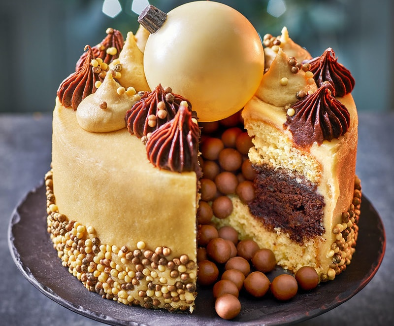 A gold coloured cake with chocolate decorations and a giant white chocolate christmas bauble on top
