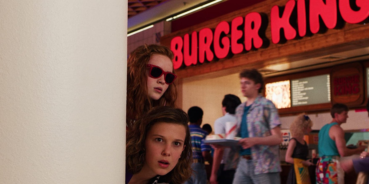 Eleven and Max in Netflix's 'Stranger Things' poke their head around a wall in the Starcourt Mall.