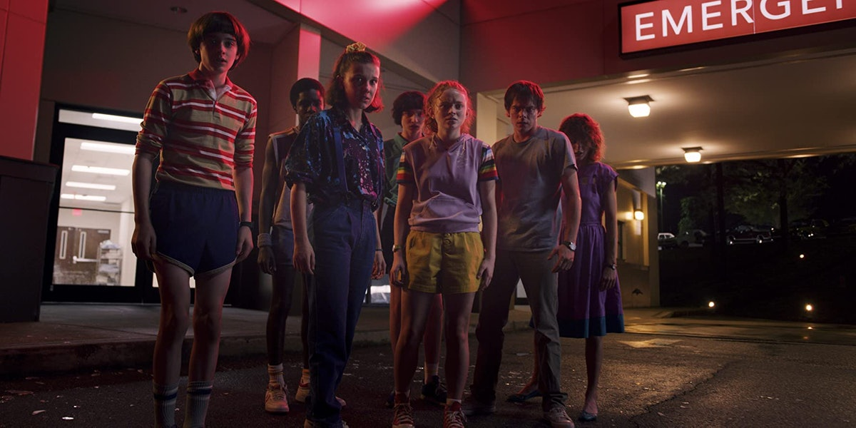 The cast of 'Stranger Things' stands outside of the Starcourt Mall in a spooky scene.