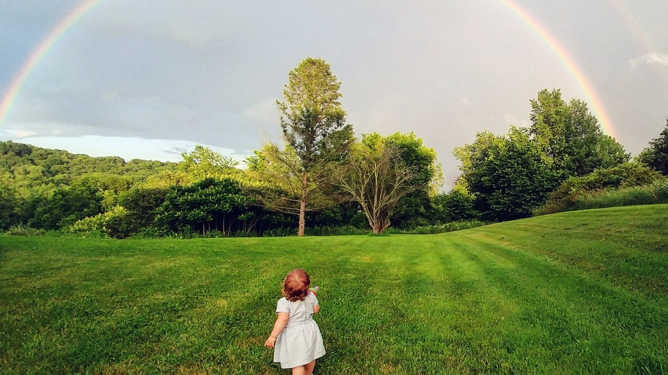 photo of baby on lawn staring at rainbow
