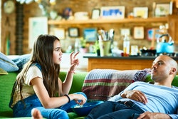 A tweenaged daughter sits sideways on couch sharing popcorn with father, who is reclined and listeni...