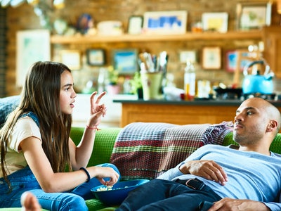 A tweenaged daughter sits sideways on couch sharing popcorn with father, who is reclined and listening.