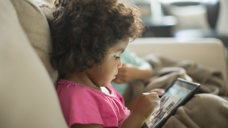 toddler on kindle tablet playing games