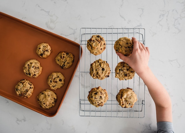 child grabbing fresh chocolate cookie from cooling rack for after-school snack