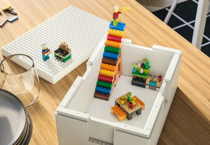 The medium sized Bygglek storage box with the lid beside it, and minifigure chef cooking over the Ik...