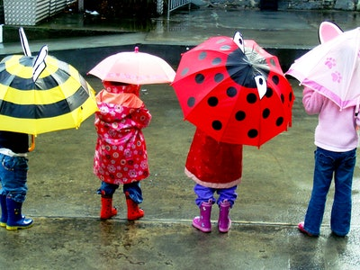children standing in the rain with colorful umbrellas