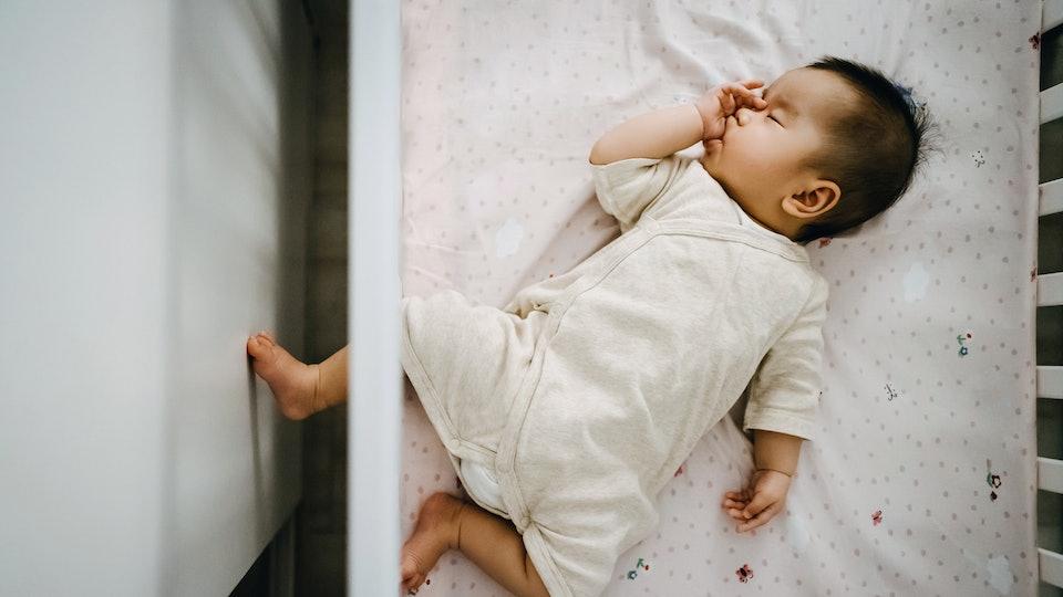 baby sleeping in crib, sucking her thumb