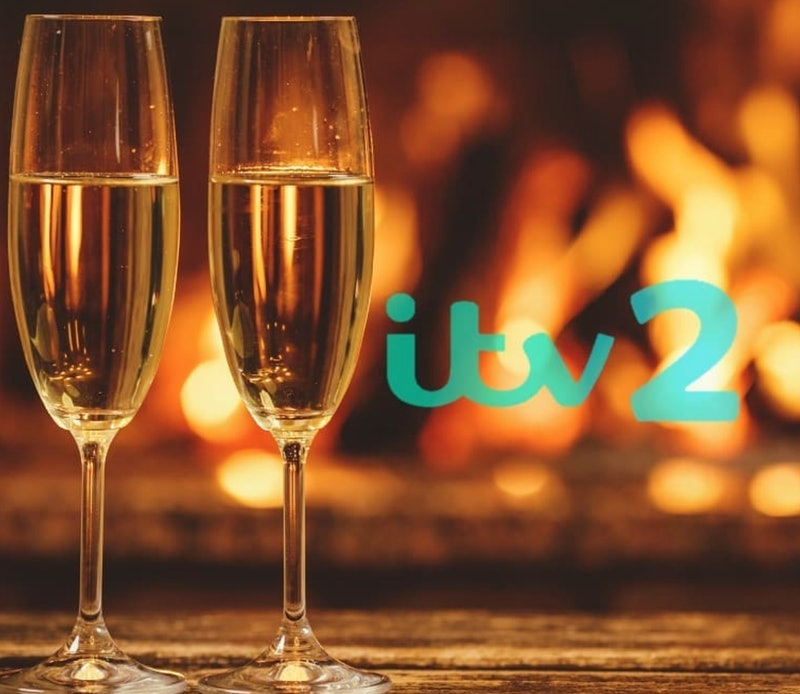 A pair of champagne flutes in front of a blurry fire in a fireplace next to turquoise sans serif text which reads: ITV 2