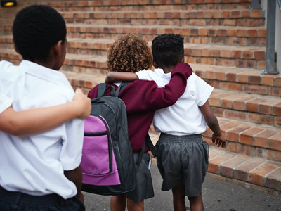 Three children in uniform walking into school with arms over shoulders