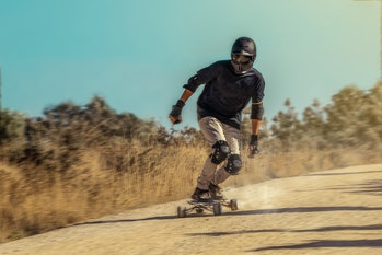 A person riding a Hunter Board on a dirt road