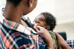 A Black mom breastfeeds her beautiful baby.