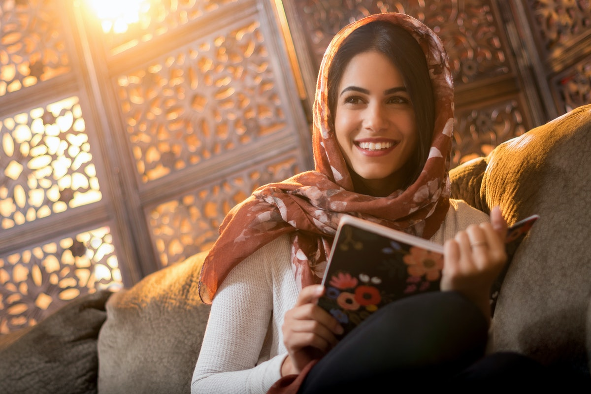 Muslim woman sitting with book
