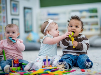 babies playing with each other and toys in a day care setting