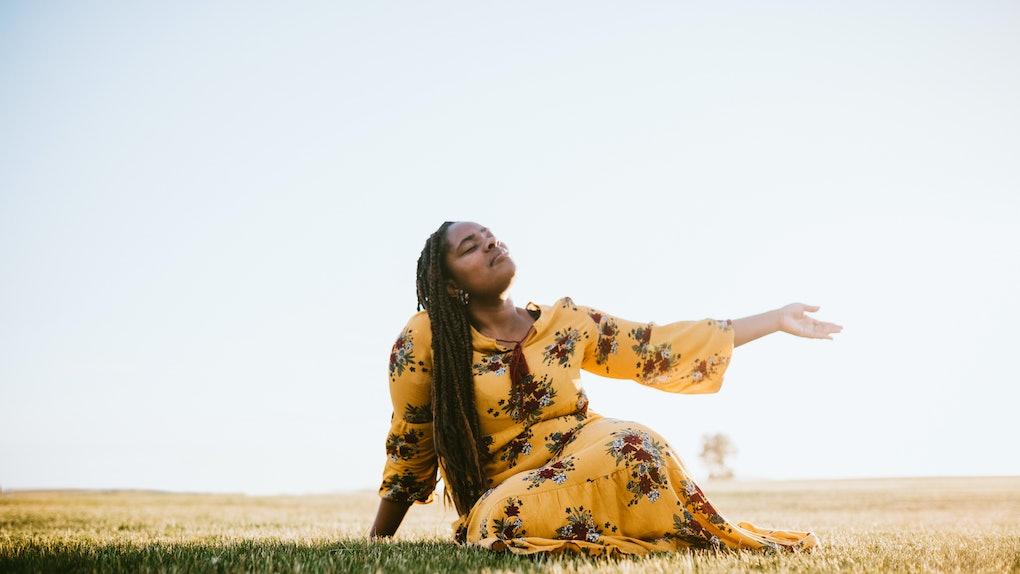 Praying Black woman in field