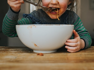 Child eating spaghetti made from slow cooker