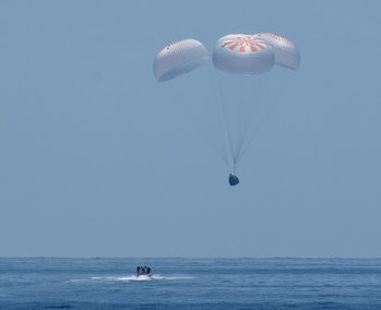 The Crew Dragon capsule returning to Earth.