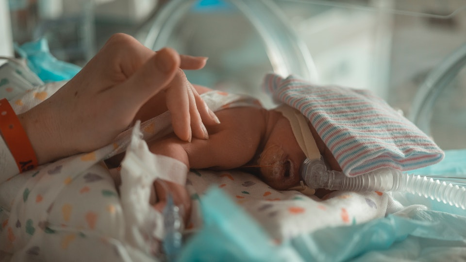 What is nicu awareness month? mother strokes her NICU baby in an isolet
