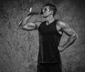 A man drinks a protein supplement shake.