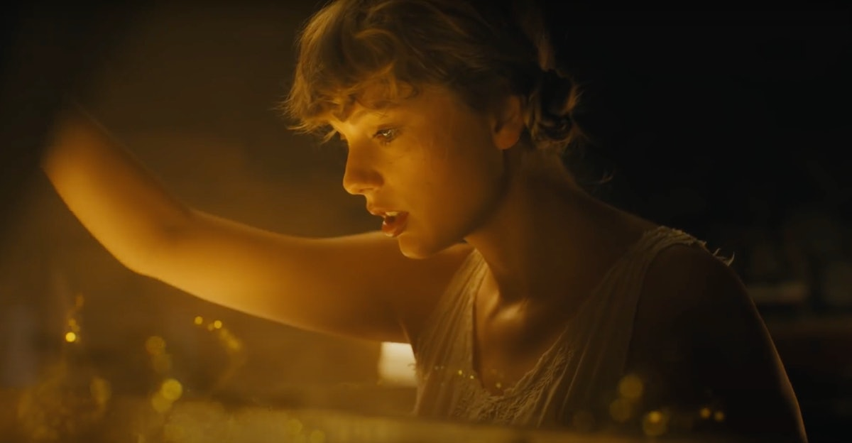 """Taylor Swift opens the top of her piano to find a gold and glittery abyss in her """"cardigan"""" music video."""