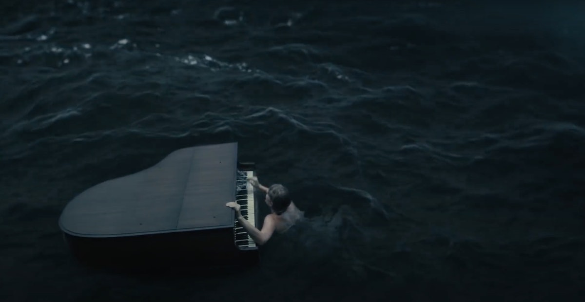 """Taylor Swift holds onto a piano that's floating in the middle of a rough ocean in her """"cardigan"""" music video."""