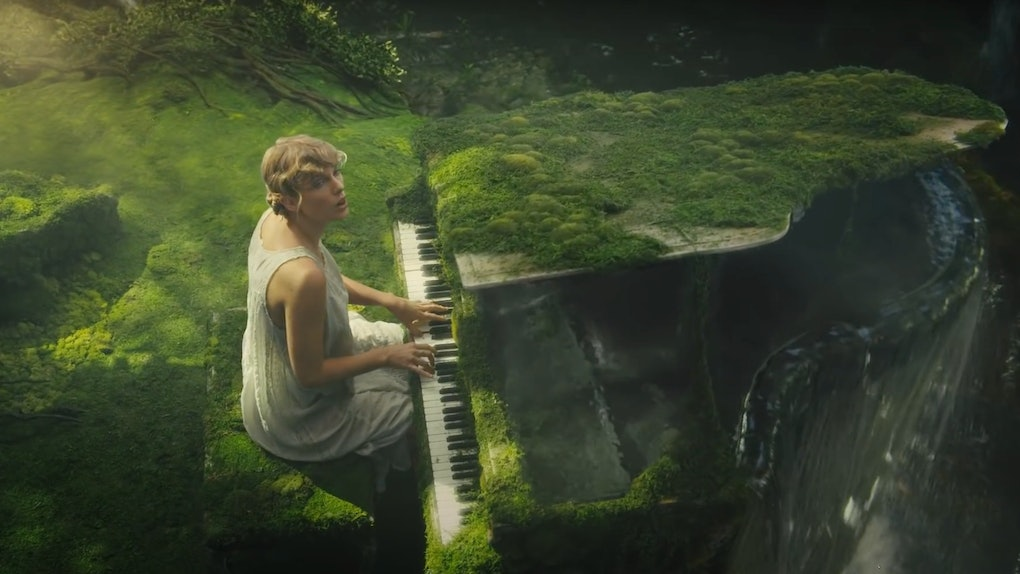 """Taylor Swift sits at a moss-covered piano in a jungle with a waterfall in her """"cardigan"""" music video."""