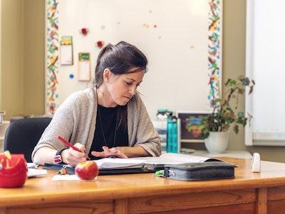 teacher grading papers at her desk