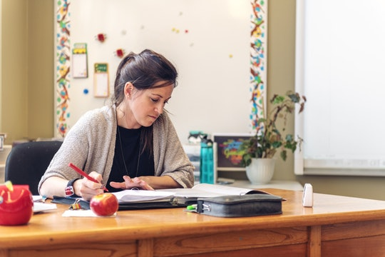 teacher grading papers at her desk