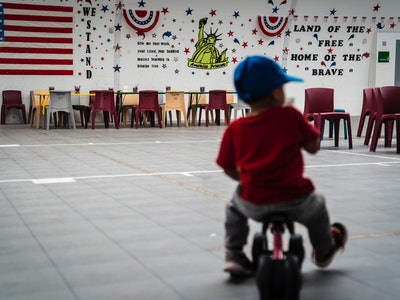 DILLEY, TX - AUGUST 23 : An immigrant child plays in front of patriotic phrases and symbols covering the walls in a gymnasium as U.S. Immigration and Customs Enforcement (ICE) and Enforcement and Removal Operations (ERO) hosts a media tour at the South Texas Family Residential Center, which houses families who are pending disposition of their immigration cases on Friday, Aug 23, 2019 in Dilley, TX. (Photo by Jabin Botsford/The Washington Post via Getty Images)