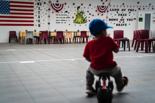 DILLEY, TX - AUGUST 23 : An immigrant child plays in front of patriotic phrases and symbols covering...