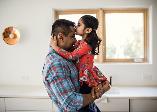 A girl kisses her father's forehead