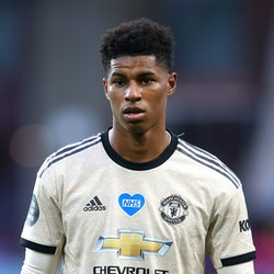 Marcus Rashford pictured playing football in a light gold and blue shirt