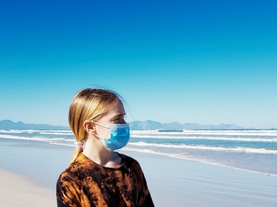 Young girl on beach wearing surgical mask, looking out at the ocean